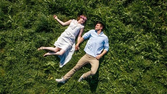 Blick von oben auf Lucy (Jennifer Siemann, l.)und Paul (Sandro Kirtzel, r.), die auf einer saftigen Wiese liegen.