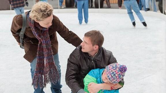 Katja und Martin (Florian Lukas, M.) eilen Anna (Hedda Erlebach, r.) zu Hilfe, die beim Schlittschuhlaufen gestürzt ist.