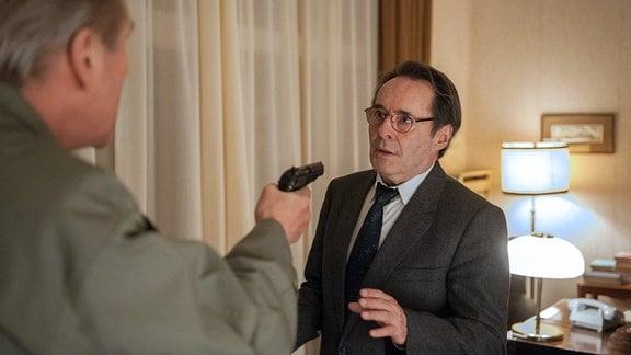 Kulisch (Michael Kind, l.) bedroht Hans (Uwe Kockisch, r.) mit der Pistole.