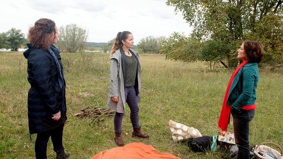 Astrid (Claudia Schmutzler, r.), Sabine (Marianne Graffam, l.) und Tina (Katja Frenzel, M.) wollen den Mauerfall am Elbufer feiern.  Vor ihnen liegt eine Decke auf der Wiese.