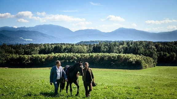 Christoph (Dieter Bach, l.) undt Tim (Florian Frowein, r.) gehen - ein Pferd führend - über eine Wiese. Hinter ihnen ein Wald.