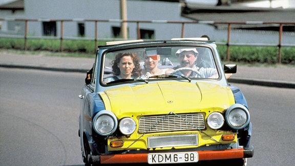 """Der sächsische Deutschlehrer Udo (Wolfgang Stumph) kommt mit Gattin Rita (Marie Gruber, re.) und Tochter Jacqueline (Claudia Schmutzler) gerade aus dem Italienurlaub zurück. Der """"trabant"""" sieht arg lädiert aus. (andersfarbige Kühlerhaube, angbundene Sztoßstange)"""