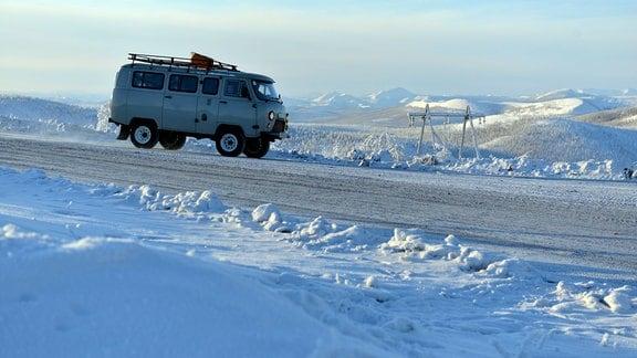 Kleinbus auf einer Eispiste in einer verschneiten Umgebung.