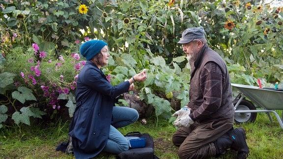 Astrid (Claudia Schmutzler, l.) und  Bruno (Wolfgang Häntsch, r.)knien auf einer Wiese.