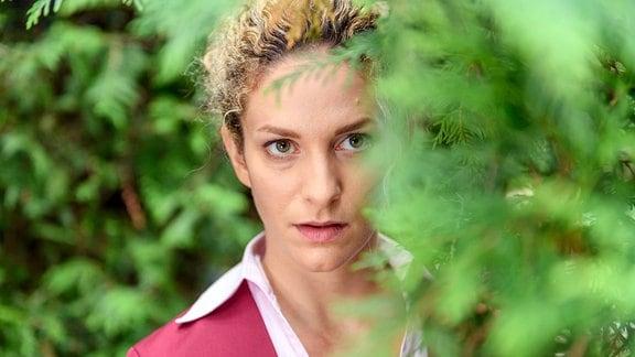 Franzi (Léa Wegmann) lugt hinter einem Busch hervor.