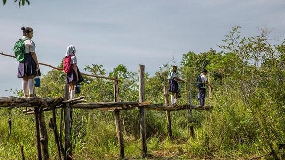 Schüler klettern über eine aus Rundhölzern bestehende und unsicher wirkende Brücke.