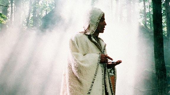 Yarpen (Derval de Faria)  - in einen weißen Umhang gehüllt - vor einem Lichtspiel der Sonne.