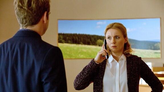 Nora (Winnie Böwe, rechts) telefoniert. Vor ihr steht Dr. Timotheus von Hatzfeld (Tom Radisch, links) steht vor ihr.
