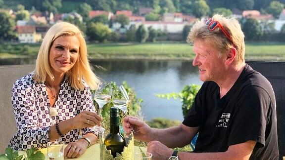 Uta Bresan stößt mit dem Winzer Wolfgang Winn mit einem Glas Wein an.
