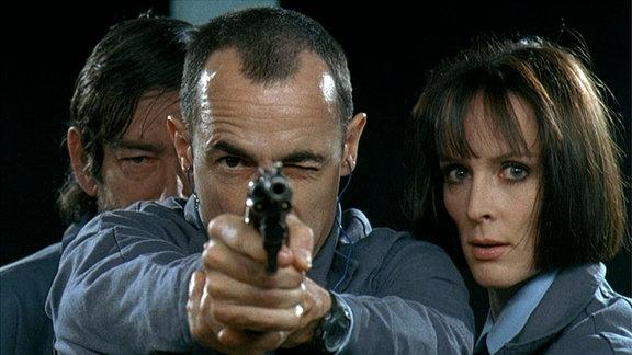 Der neue Sicherheitsmann Alexandre Demarre (Albert Dupontel, Mitte, mit einer Pistole zielend) erstaunt den Waffenmeister (Michel Trillot, hinten) und seine Kollegin Nicole (Claude Perron) mit seinen Schießkünsten.