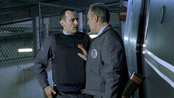Der alternde Sicherheitsmann Bernard (Francois Berleand) erklärt dem Neuling Alexandre Demarre (Albert Dupontel, li.), dass er jederzeit bereit ist, sich mit Angreifern und Räubern einen Kleinkrieg zu liefern.