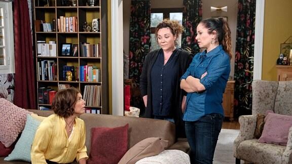 (Claudia Schmutzler, links) sitzt; Tina (Katja Frenzel, rechts) und Sabine (Marianne Graffam) stehen in einem Wohnzimmer..