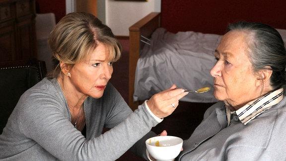 Agnes Wieland (Christiane Hörbiger) reicht  ihrer dementen Mutter Rosa Fischmeister (Maria Urban, rechts)einenen Löffel.