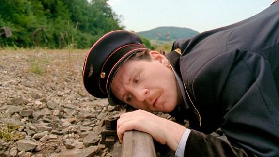 Milosz (Georg Tryphon) lauscht an den Gleisen.