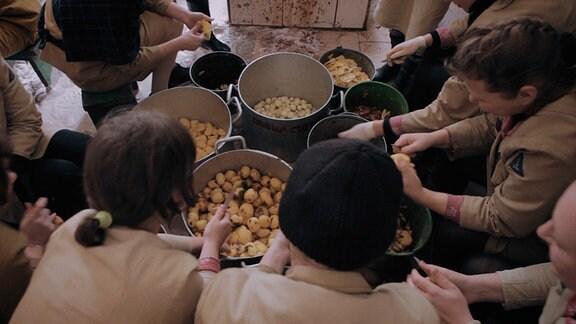 Die Frauen arbeiten nicht nur in der Fabrik, sie haben zusätzlich auch Küchendienst: Jeden Tag müssen 800 kg Kartoffeln geschält werden.