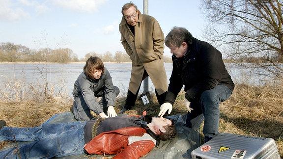 Noch ein Toter! Schmücke (Jaecki Schwarz) und seine Kollegen Schneider (Wolfgang Winkler) und Rosamunde Weigand (Marie Gruber) an der Leiche Heiko Remscheidts (Steffen Groth).