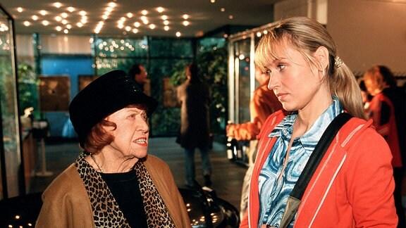 Tante Olga (Brigitte Mira, li.) mit der Astrologin Lena (Anica Dobra) in einem Ausstellungsraum.