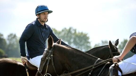 Tim (Florian Frowein, l.) - mit Helm - sitz auf einem Pferd.