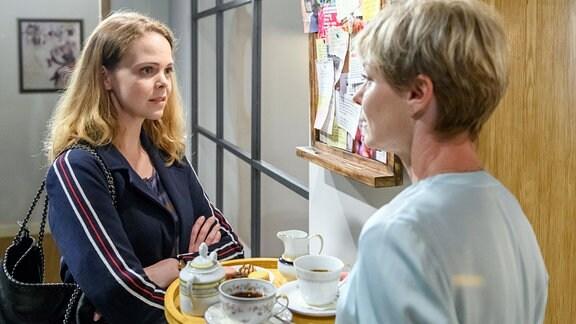 """Lucy (Jennifer Siemann, l.) bemerkt vor Linda (Julia Grimpe, r.), wie sehr den Bichlheimern der """"Engel"""" fehlt, als sie die vielen Wünsche an der Pinnwand liest."""