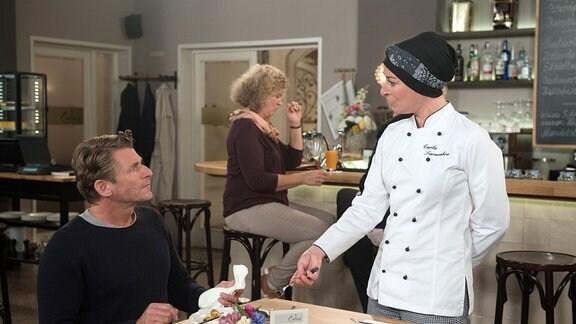 Carla (Maria Fuchs, rechts) steht an einem Tisch. Henning (Herbert Ulrich, links)  sitzt an ihm. Im Hintergrund sitzt eine Frau an einer Bar.