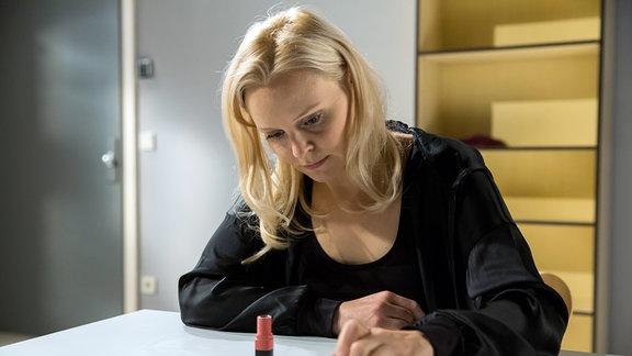Annabelle (Jenny Löffler) sitzt an einem Tisch.