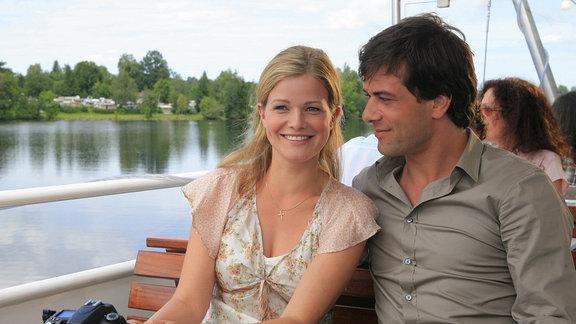 Marie (Mira Bartuschek) unternimmt mit dem Fotografen Niklas (Kai Schumann) eine Tour auf einem See. Sie sitzen auf einem Binnenschiff. Das Gewässetr und das Ufer sind zu erkennen.