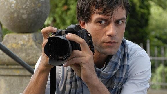 Der Fotograf Niklas (Kai Schumann) hält einen Fotoapparat in der Hand und blickt an ihm seitlich vorbei.