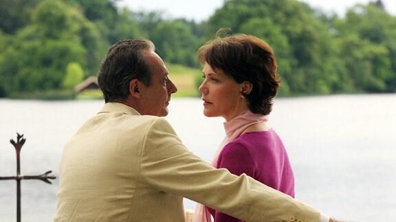 Carla (Janina Hartwig) und der Kunstprofessor Peter Blumfeld (Daniel Friedrich) sitzen auf einer Bank vor einem See. Sie blicken sich an.