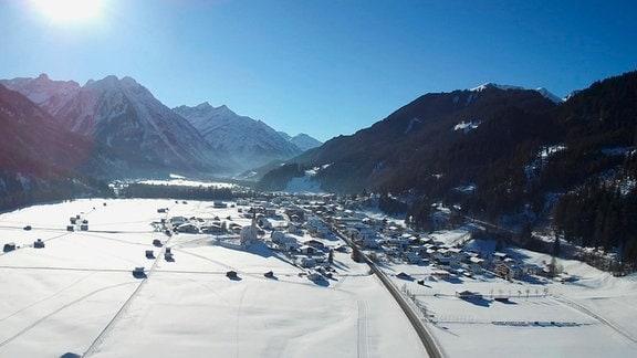 Blick auf ein Dorf im verschneiten Lechtal. Im Hintergrund Alpengipfel.