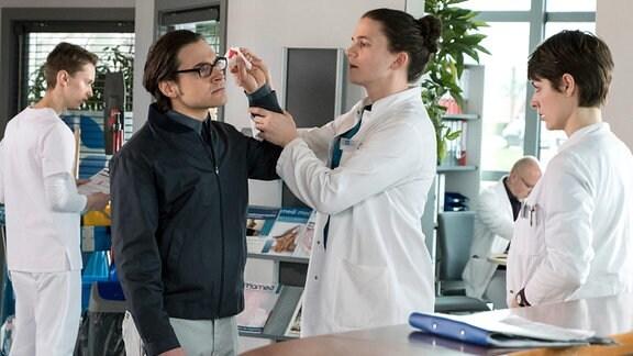 Torsten Kars (Johannes Klaußner, 2.v.l. mit Komparse, h.) hat ein Explosionstrauma erlitten, als ein Böller direkt neben seinem Ohr geplatzt ist. Den Assistenzärzten Tom Zondek (Tilman Pörzgen, 2.v.r.) und Dr. Theresa Koshka (Katharina Nesytowa, r.) fällt das autistische Verhalten des Patienten auf.