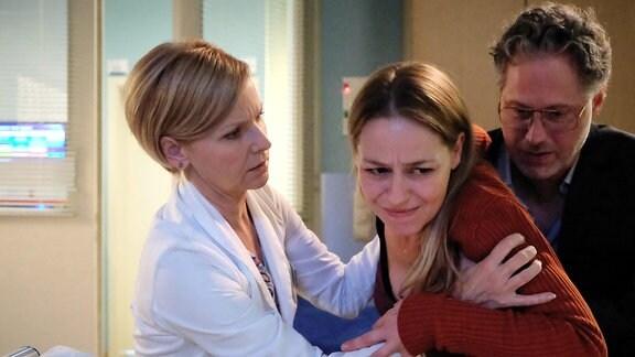 Bernadette Winkler (Theresa Scholze, mi.) hat sich bei einem Sturz einen stabilen Wirbelbruch zugezogen. Sie braucht Ruhe und langsame, ruhige Bewegungen. Doch Jan Martus (Jörn Knebel, re.) fordert von ihr Schadensersatz, da sie bei ihrem Sturz seinen Laptop beschädigt hat und Schmerzensgeld, für eine Verletzung an seinem Finger durch eine Glasscherbe. Jan provoziert Bernadette dermaßen, dass sie eine zu schnelle Bewegung macht und plötzlich mit Schmerzen zusammen bricht. Dr. Kathrin Globisch (Andrea Kathrin Loewig, li.) kommt gerade rechtzeitig, um sie aufzufangen.