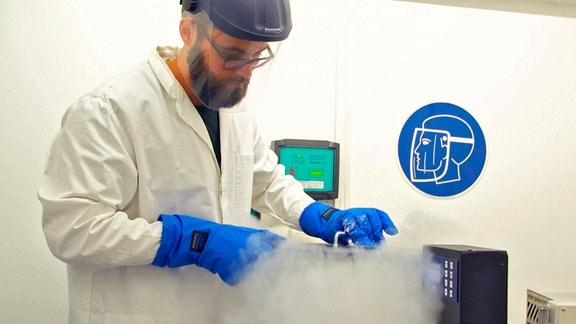 Ein Wissenschaftler arbeitet in seinem Labor. Aufsteigender Stickstoffnebel verdeutlicht, dass die Arbeiten mit stark gekühlten Präparaten ablaufen.