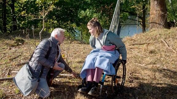 Thomas (Gerry Hungbauer, llinks) kniet seitlich neben (Clara Apel, rechts), die im Rollstuhl sitzt.