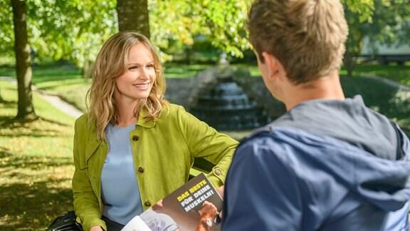 Jessica (Isabell Ege, l.inks und Paul (Sandro Kirtzel, rechts) sitzen <auf einer Bank in einem Park..