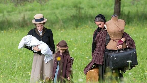 Katharina (Friederike Becht, li.) geht mit ihrer kleinen Tochter Maria (Helena Schönfelder), ihrem Sohn und hrer Mutter Christiane (Ursula Strauss) über eine Wiese mit höherem Gras