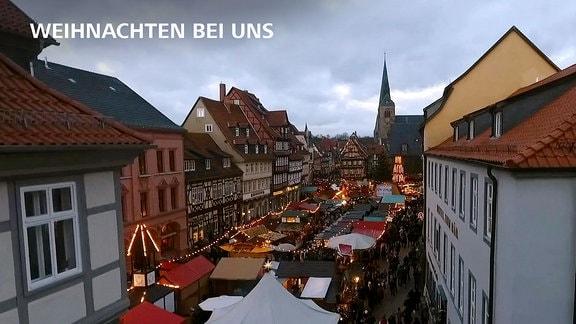 Blick auf eine Quedlinburger Straße mit Verkaufsständen, zahlreichem Publikum und wehachtlicher Aiusschückung