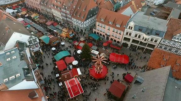 Blick auf einen Quedlinburger Platz und eine Innenstadtstraße mit zahlreichen Verkaiufsständen, weihnachlichem Schmuck und zahlreichen Besuchern