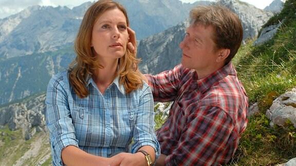Juliane (Karin Thaler) und Philipp (Michael Fitz) vor den Hochalpen; er streicht über ihr Haar.