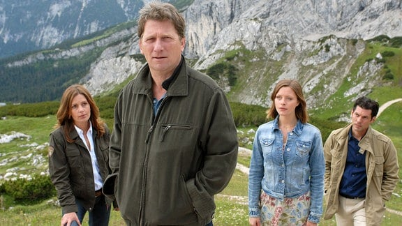Philipp (Michael Fitz, vorn),  Juliane (Karin Thaler, links), Sarah (Alma Leiberg) und Lukas (Gregory Brain Waldis, rechts)stehen am Fuss kahler Felsen.