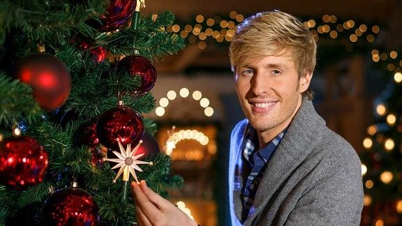 Maximilian Arland neben einem Weihnachtsbaum