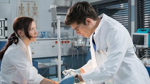 Nach einem Unfall im Labor behandelt Ben (Philipp Danne, r.) Sina Liebig (Isabel Bongard, l.) in der Notaufnahme.