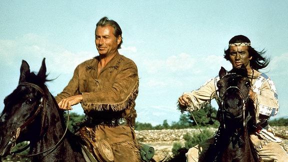 Seite an Seite jagen die Blutsbrüder Winnetou (Pierre Brice) und Old Shatterhand (Lex Barker) eine Verbrecherbande. Beide sind beritten.