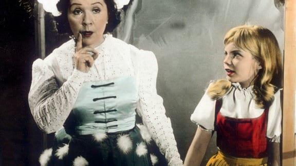 Frau Holle (Lucie Englisch, links) erklärt der kleinen Goldmarie (Madeleine Binsfeld), welche Pflichten sie hat.