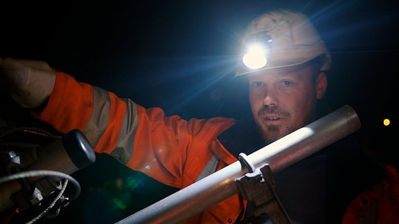 Paul Klinger mit Helm und Stirnlampe in der Dunkelheit bei der Arbeit.