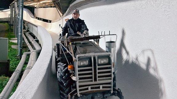 Eismeister Mende glättet mit dem Traktor auf der Bobbahn alle Flächen.