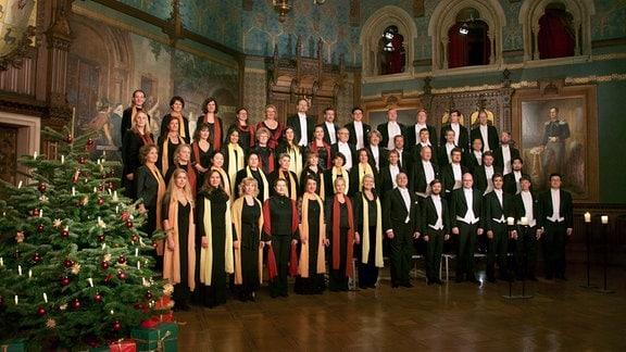Der MDR-Rundfunkchor steht neben einem Weihnachtsbaum in einem Prunkraum des wernigeröder Schlosses.