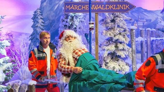 Der Werihnachtsmannn (frank Svchöbel  wird durch eine verscheite Kunstlandschaft auf einer Trage von zwei Nofall-Sanitätern getragen.