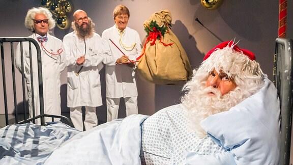 """Motiv """"Im Krankenzimmer"""" Prof. Balthasar, OA Melchior, Dr. Kaspar stehen in weißer Krankenhausbekleidung hinter einem schlichten Stahlrohrbett, in dem Frsank Schölbel lieg. Frank Schöbel trägt ein Weihnachtsmann-Kostüm."""