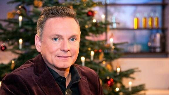 Axel Bulthaupt vor einem Weihnachhtsbaum.