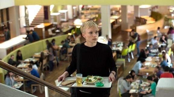Die Psychologiestudentin Trude (Lise Risom Olsen) sucht in der Cafeteria der Uni einen freien Platz.